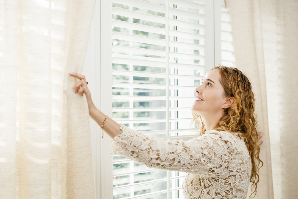 A homeowner decorates her window coverings after reading tips from Interior Essentials